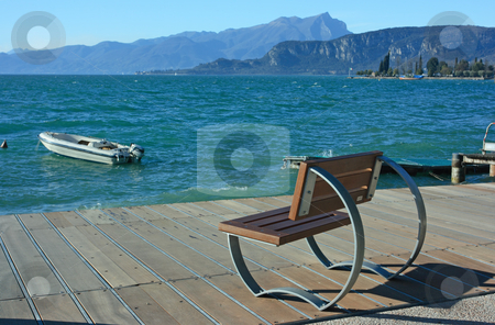 Lake Garda stock photo, Bench to sit on adn to observe colorful lake Garda with boats and mountains on horizon by Natalia Macheda