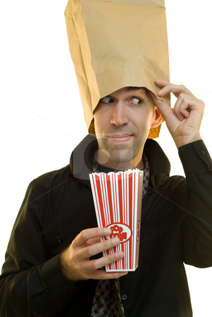 Snacking In Private stock photo, A young businessman wearing a paperbag trying to eat his popcorn in private by Richard Nelson