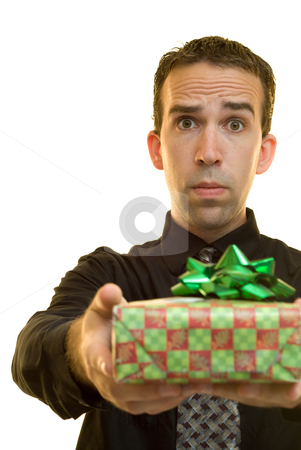 Corporate Christmas stock photo, A young businessman holding out a Christmas present to someone by Richard Nelson