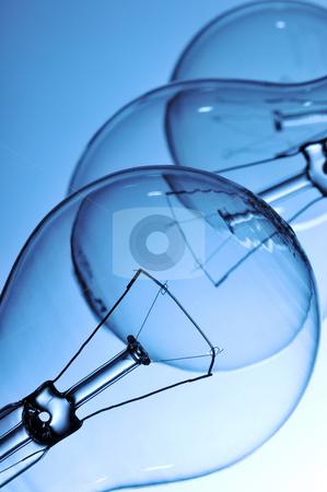 Lightbulbs stock photo, Close-up of three lightbulbs isolated on blue by Csaba Zsarnowszky