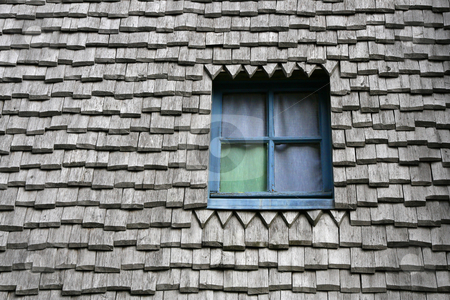 Colored window stock photo, Colored window on a ancient wooden roof by Tilo