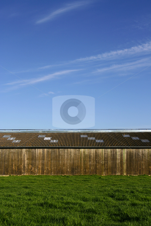 Wooden storehouse stock photo, Wooden storehouse in the countryside, with a blue sky background by Tilo