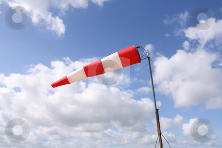 Windsock (horizontal) stock photo, Red and white windsock blows against a blue sky by Tilo