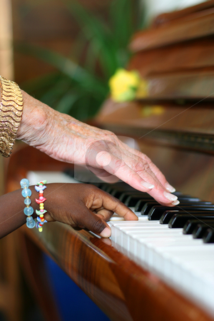 Ebony and Ivory Harmony stock photo, One older white hand and one younger black hand playing the piano by Tilo