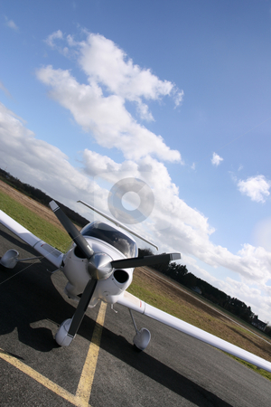 Inclined white plane stock photo, Inclined front view of a white plane on the runway by Tilo