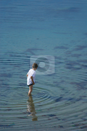 In a clear water stock photo, Young boy standing and looking in the clear water (vl) by Tilo