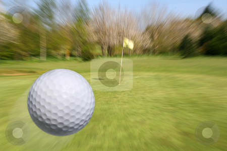 Flying golf ball stock photo, Golf ball flying to the cup. Zooming to the hole. by Tilo