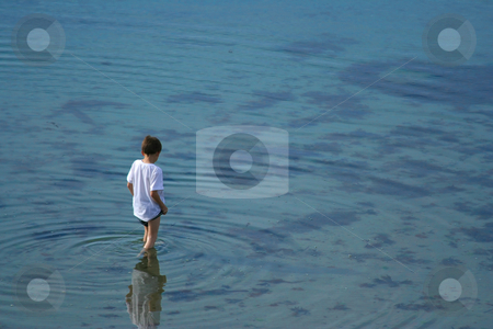 In a clear water stock photo, Young boy standing and looking in the clear water (hz) by Tilo