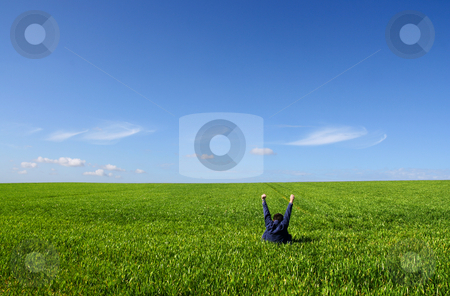 Self victory stock photo, A man sitting alone in a green field, with lifted V arms by Tilo