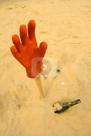 Glove on the end of a broomstick stock photo, Assistance needed, hanging glove and bottle in the sand by Tilo