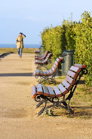 Public bench stock photo, Public bench near the ocean, woman in the background by Tilo
