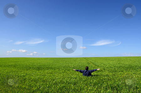 Sanity equilibrium stock photo, A man sitting alone in a green field, with open arms by Tilo