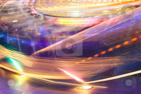 Spinning lights stock photo, Blur neon lights in amusement park by Tilo