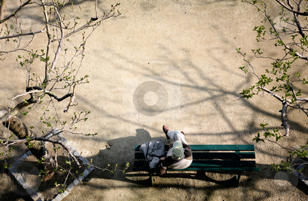 Thinking on a bench stock photo, Top view of a man sitting on a bench by Tilo