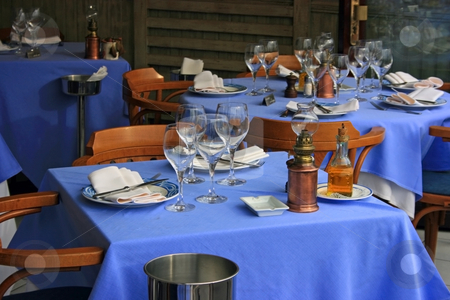 Table appointments stock photo, Setting of restaurant tables covered with blue table-clothes outdoors includes goblets, plates, napkins, ashtray, oil in a bottle, bucket with ice to refresh wine, and romantic retro lamp by Natalia Macheda
