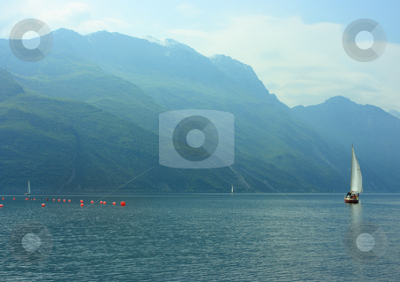 Sailboat on Garda lake stock photo, Sailboat on Garda lake early hazy morning by Natalia Macheda