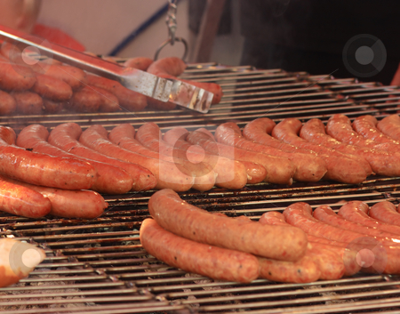 Sausages on grill stock photo, Cooking sausage on grill. Focus on the central row of sausages by Natalia Macheda