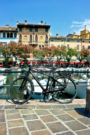 Bicycle in Desenzano stock photo, Bicycle in Desenzano near Garda lake with beautiful venetial houses on the background by Natalia Macheda