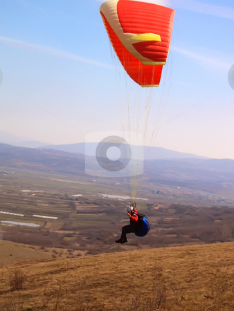 Paragliding stock photo, Paragliding airborne over valley with hills in distance by Ivan Paunovic