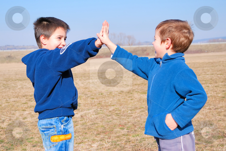 Boys giving high five hands stock photo, Boys playing gimme five outside on a sunny day by Ivan Paunovic