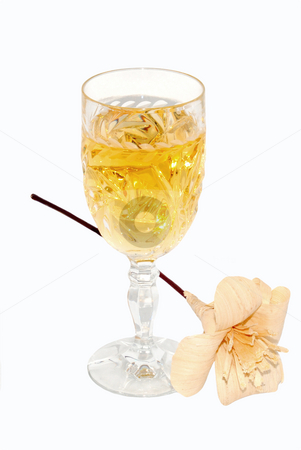 White wine in a crystal glass stock photo, White wine in a crystal glass and a flower over white by Ivan Paunovic