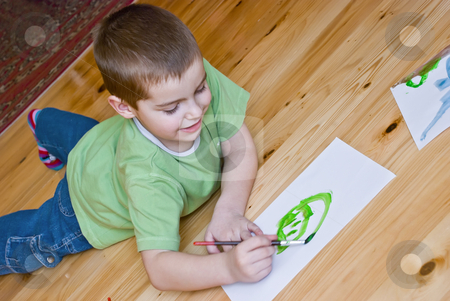 Boy painting stock photo, A boy is painting on the floor by Ivan Paunovic