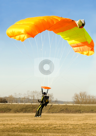Orange parachute stock photo, An orange parachute is landing softly on a sunny day by Ivan Paunovic