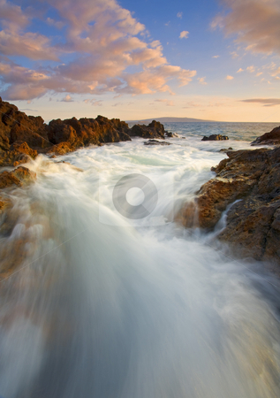 Tidal Surge stock photo, Lava rock off the South coast of Maui with the light of the setting sun illuminating the clouds and rocks alike as the incoming tides surge past the rocks. by Mike Dawson