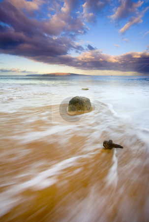Pulled to the Sea stock photo, An Old cleat from a long ago eroded jetty is swept over by the ebbing tide as the sun rises over this South MAui Beach with Kahaloowe in the distance. by Mike Dawson