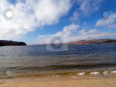 Wide angle view of small cove with water and clouds stock photo, Water beach blue sky and white clouds  small waves by Jeff Cleveland