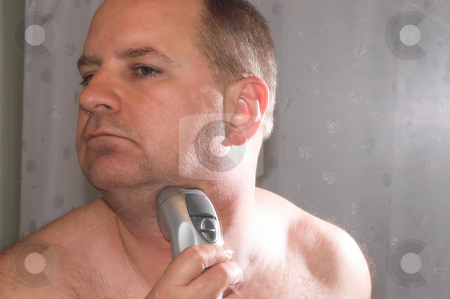 Shaving Man stock photo, A man shaving his face in the morning. by Robert Byron