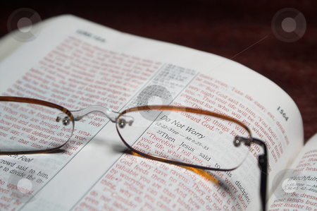 Bible Verse stock photo, Scriprure verses inside of a holy bible and reading glasses. by Robert Byron