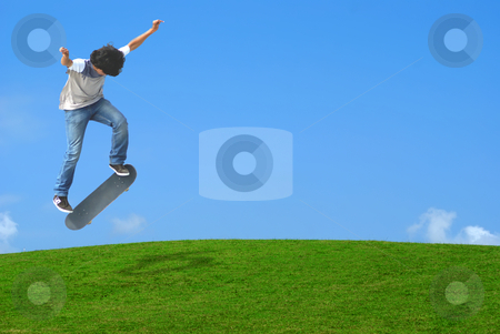 Skater stock photo, Young skater jumping over a green  hill. by Serge VILLA