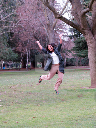 Woman jumping stock photo, Smiling jump with arms up amid trees and grass by Jeff Cleveland