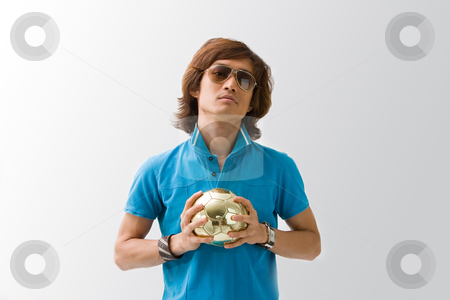 Sporty Asian guy with ball stock photo, Sporty Asian guy in blue t-shirt holding a small golden soccer ball with both hands, isolated by Paul Hakimata