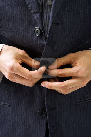 Suit and hands stock photo, Hands un-buttoning a gray pinstriped business suit closeup by Paul Hakimata