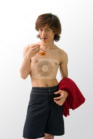 Asian guy in swimwear stock photo, Asian guy in black swimwear with orange sunglasses and a red towel hanging over his arm, isolated by Paul Hakimata