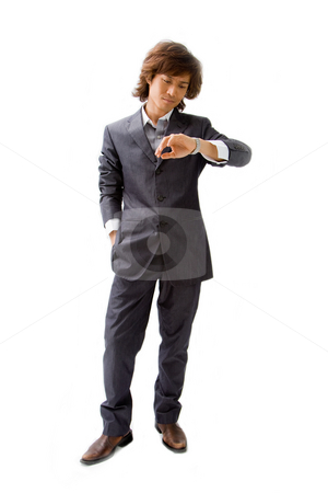 Young Asian business man stock photo, Young Asian business man dressed in a gray pinstripe suit with hand in pocket and looking at his watch, isolated by Paul Hakimata