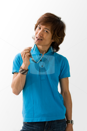 Happy Asian guy with sunglasses stock photo, Happy Asian guy in blue t-shirt holding sunglasses and biting on it, isolated by Paul Hakimata