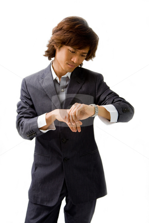 Young Asian business man stock photo, Young Asian business man dressed in a gray pinstripe suit checking time by looking at his watch, isolated by Paul Hakimata