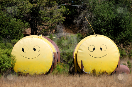 Smiley Face Tanks stock photo, Two Tanks with Yellow Smiley Faces Painted on Them Standing Next to Each Other in a Field by Denis Radovanovic