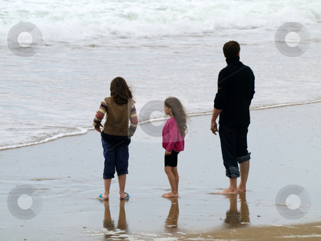 Family on holidays at the beach stock photo, Father and his two daughters  at the beach by Laurent Dambies