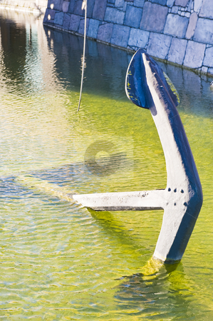 Old large anchor in shallow water stock photo, An old large anchor lying in shallow water at the docks. by Nicolaas Traut