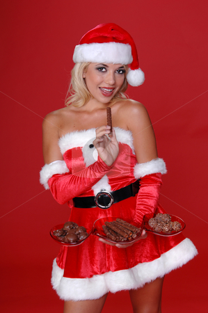 Christmas Chocolates stock photo, Sexy Mrs Santa nibbles on a piece of candy from tray of Christmas Chocolates by Robert Deal