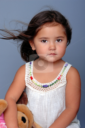 Thoughtful child stock photo, Little girl sitting on a grey background and holding a stuffed toy by Robert Deal