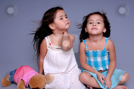 Beautiful Girls stock photo, Two little girls sitting together on a grey background and playing model. One girl holding a stuffed toy by Robert Deal