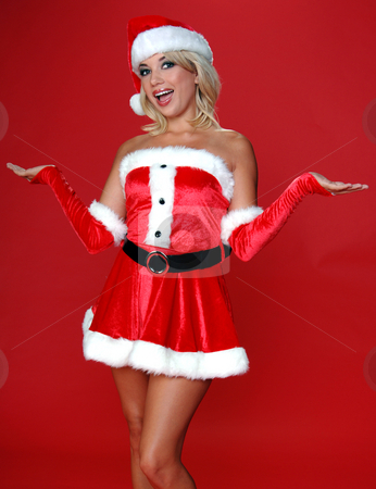 Mrs. Santa Shrugs stock photo, Sexy blond Mrs Santa in a red velvet suit shugs as if to say