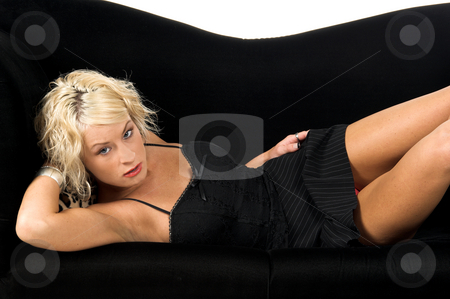 Pretty Blond Laying On Couch stock photo, Pretty blonde with short hair and a nice smile laying on a black and lepoard print couch by Robert Deal