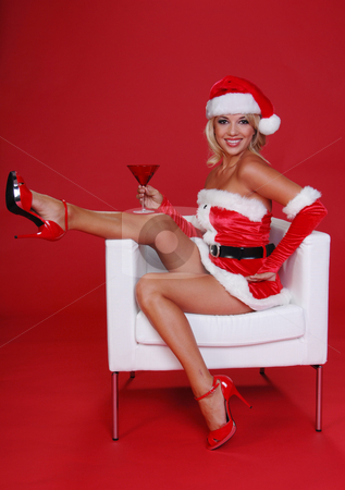 Christmas Martini stock photo, After a long days work Santa's sexy helper throws her feet up and relaxes with a Martini in a Christmas Red glass. by Robert Deal