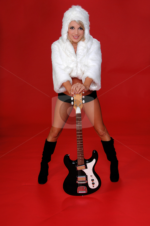 Rock N Roll  Snow Bunny stock photo, Sexy blond snow bunny in a white furry coat and hat and black hot pants over a red background with an electric guitar by Robert Deal